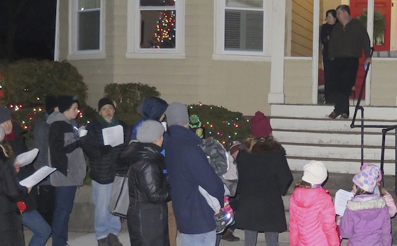 The carolers serenade some residents on Sixth Street.