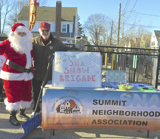 Santa helps Kerry Kohring, SNA vice president, publicize the snow brigade at the Hope Street holiday festival Sunday. Note the food truck banner behind them.