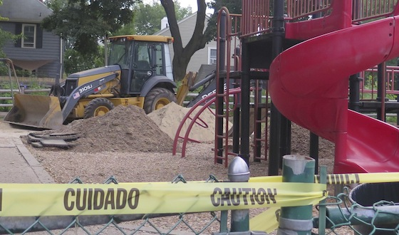 A backhoe moves sand around in the Summit Avenue park playground.